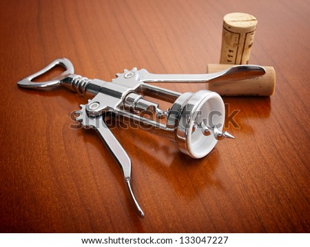 Corkscrew and two corks on a wooden background. - stock photo