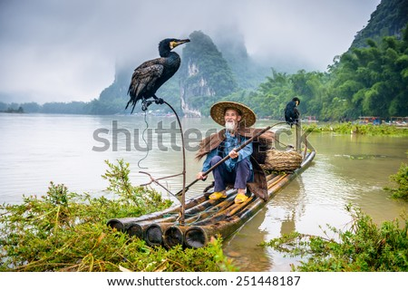 Cormorant fisherman and his bird on the Li River in Yangshuo, Guangxi, China.  - stock photo