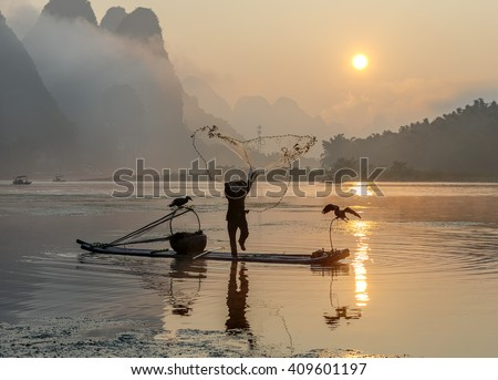 Cormorant fisherman throws a net with ancient traditional chinese bamboo boats at sunrise - Xingping, China - stock photo
