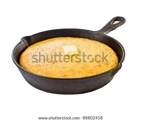 Corn bread in iron skillet isolated on white - stock photo
