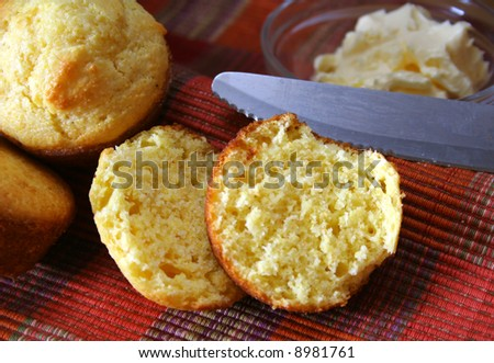 corn bread muffins with knife and butter in the background. - stock photo