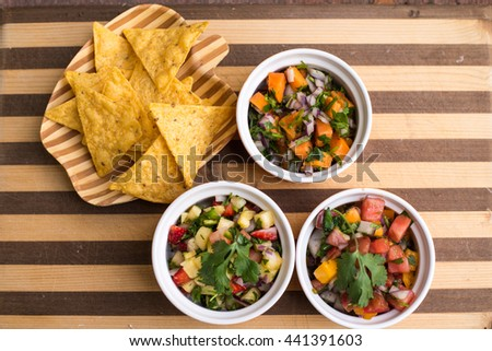 Corn chips and three different salsas on a striped wooden board  - stock photo