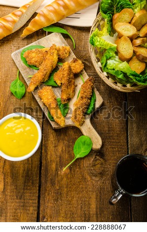 Corn crusted Chicken Tenders with spinach and toast, honey-dijon mustard dip, homemade bread baguette - stock photo