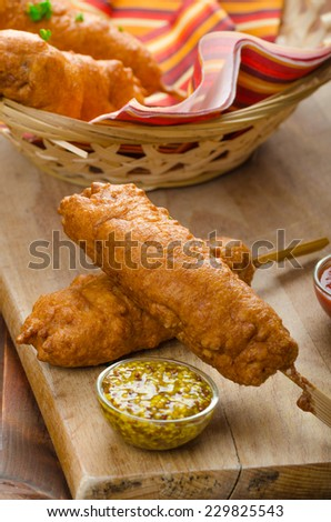 Corn dog with three sauces, chilli, mayonnaise with herbs and whole grained mustard - stock photo