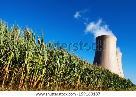 Corn field against nuclear power plant Conceptual image - stock photo