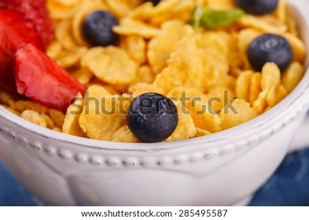 Corn flakes and fresh berries, for Breakfast. selective focus - stock photo