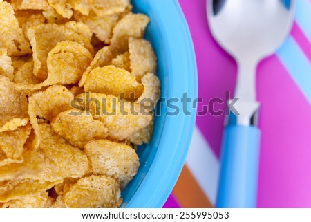 Corn flakes detail on a colorful kitchen table. Image with shallow depth of field. - stock photo