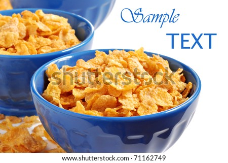 Corn flakes in blue ceramic bowls on white background with copy space.  Macro with shallow dof. - stock photo