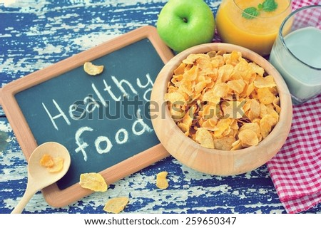 Corn flakes in wooden bowl with healthy food word on small blackboard,healthy food concept. - stock photo