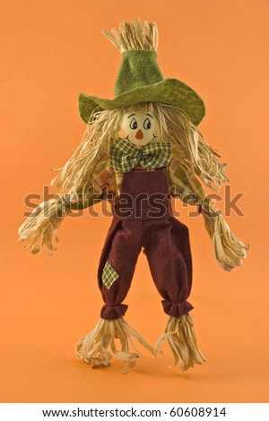 Corn husk scarecrow farmer doll on orange background in vertical format for Halloween or Thanksgiving theme - stock photo