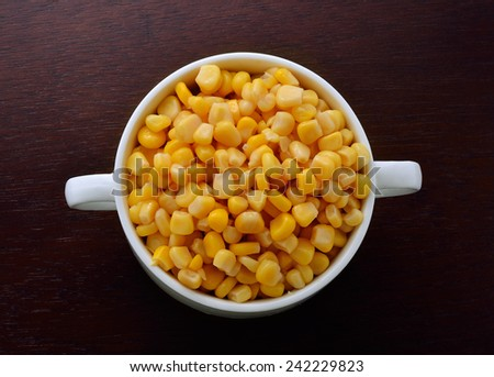 corn in bowl isolated on wooden background - stock photo
