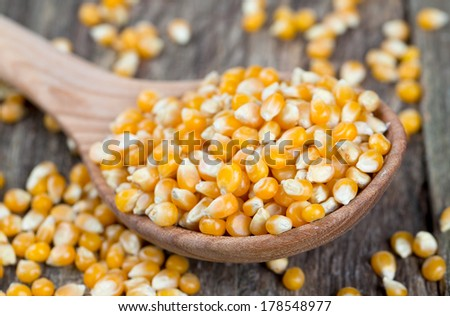 corn in wooden spoon on rustic surface - stock photo