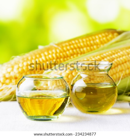 Corn oil and corn cobs on a garden table. - stock photo