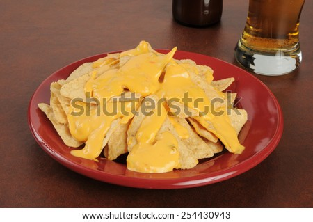 Corn tortilla chips with nacho cheese sauce and a glass of beer - stock photo