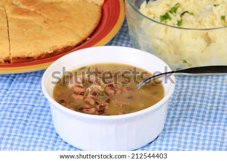 Cornbread and mashed potatoes fronted by bowl of black-eyed peas seasoned with fat back and bacon on blue gingham Southern Style setting. - stock photo