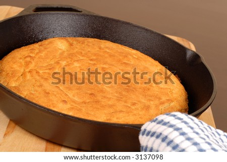 Cornbread made in a cast iron skillet resting on a cutting board - stock photo