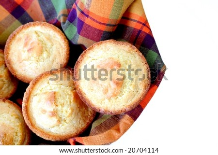 Cornbread muffins in a colorful towel isolated on a white background. - stock photo