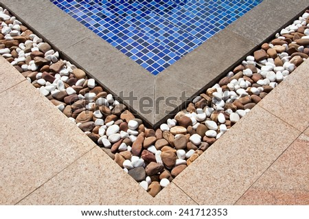 Corner of a swimming pool with decorative stones - stock photo
