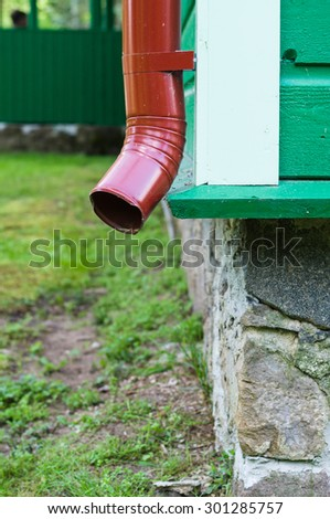 Corner of building with red metal drainpipe, architectural detail - stock photo