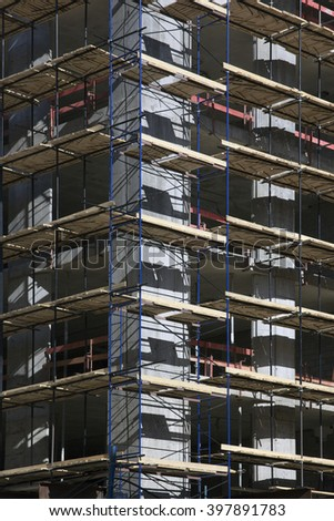corner of concrete building under construction with scaffolding in Moscow, Russia - stock photo