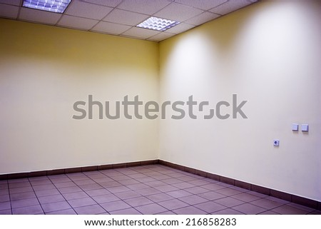 Corner of empty office room with floor of stones, ceiling, lamps and yellow walls. - stock photo