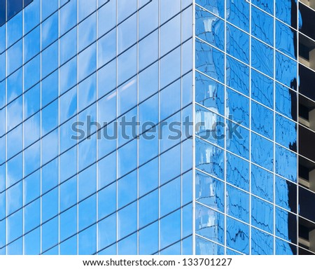 Corner of modern office building with bright blue sky reflections in windows - stock photo