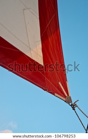 Corner of red and white jib sail with jibsheet showing - stock photo