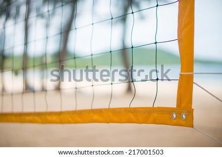 Corner of yellow volleyball net on beach among palm trees - stock photo