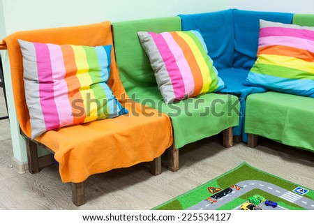 Corner sofa with colorful striped pillows in the room - stock photo