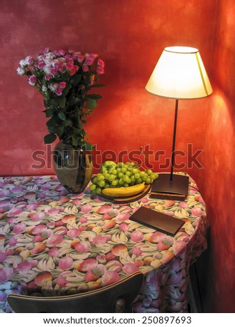 Corner table with flowers and lamp light. Indoor shot. - stock photo