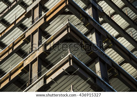 corner view detail high rise building showing steel girders under construction - stock photo