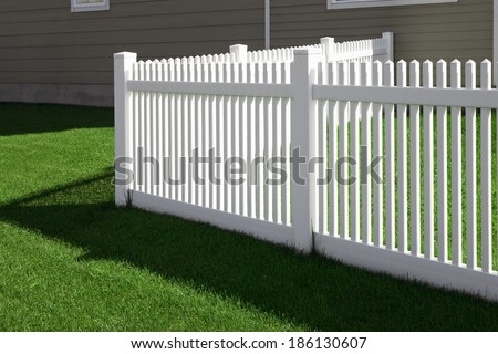 corner white fence and grass lawn near the house - stock photo