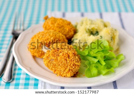 Cornflake crusted chicken pieces served with salad leaves and mashed potatoes - stock photo