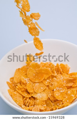 Cornflakes being poured into a bowl ready for breakfast - stock photo