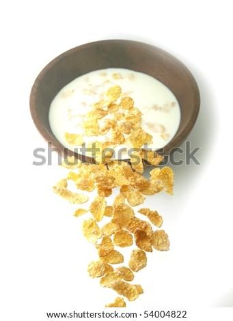 Cornflakes falling on milk - stock photo
