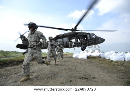 CORNING, MO - JUNE 26: Missouri National Guard soldiers airlift sandbags with a black hawk helicopter to try and reinforce a levee Sunday, June 26, 2011 near Corning, Mo. - stock photo