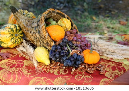 Cornucopia Harvest: A cornucopia overflows with the fruits of a fall harvest on an outdoor table full of autumn color. Seasonal, holiday concept. - stock photo