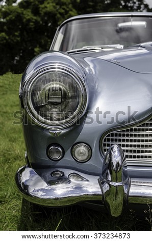 CORNWALL, UK - CIRCA JULY 2015: Classic Aston Martin DB5 blue metallic silver chrome front view of the car taken from a low angle. Vertical. Focus on headlight.  - stock photo