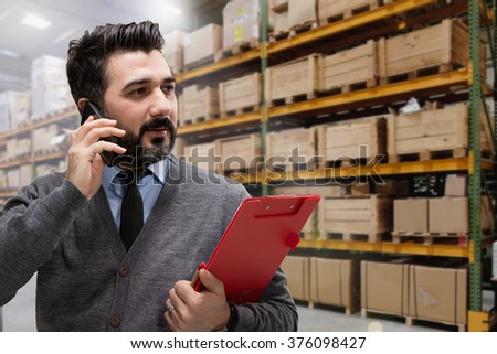 Corporate businessman using his cellphone while checking inventory in a large warehouse. - stock photo