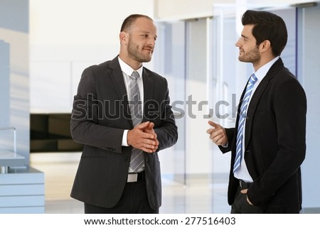 Corporate businessmen meeting and talking on office corridor. - stock photo