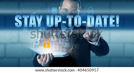 Corporate end user is pressing STAY UP-TO-DATE! on a virtual touch screen interface. Business challenge metaphor and information technology concept for keeping your IT knowledge and software current. - stock photo