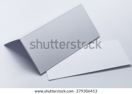 Corporate identity. Close up of a blank white paper bi-fold broshure template. - stock photo