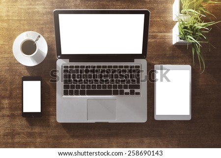 Corporate identity mock up on an hardwood desk with laptop, tablet, smartphone and a cup of coffee - stock photo
