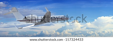 Corporate jet cruising in a cloudy sky - stock photo