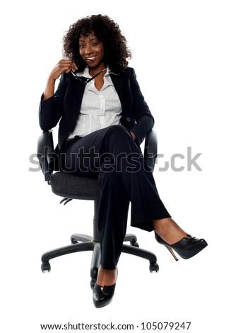 Corporate lady posing with eyeglasses in hand. Seated with crossed legs on chair - stock photo