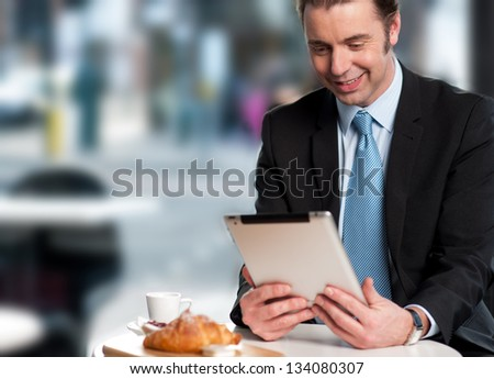 Corporate male manager reviewing business updates on his tablet device. - stock photo