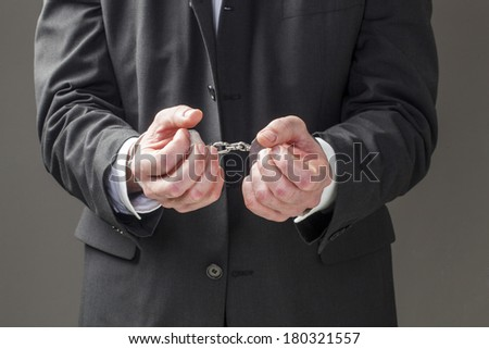 corporate man held in bracelets - stock photo