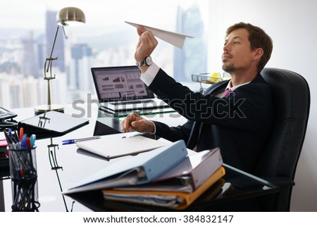 Corporate manager in modern office takes a break and prepares a paper airplane. The bored man dreams of his next vacations and leans back on his chair - stock photo