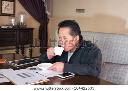 Corporate middle-aged man in a cafe watching reports - stock photo