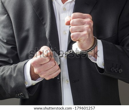 corporate offense with man in handcuffs - stock photo